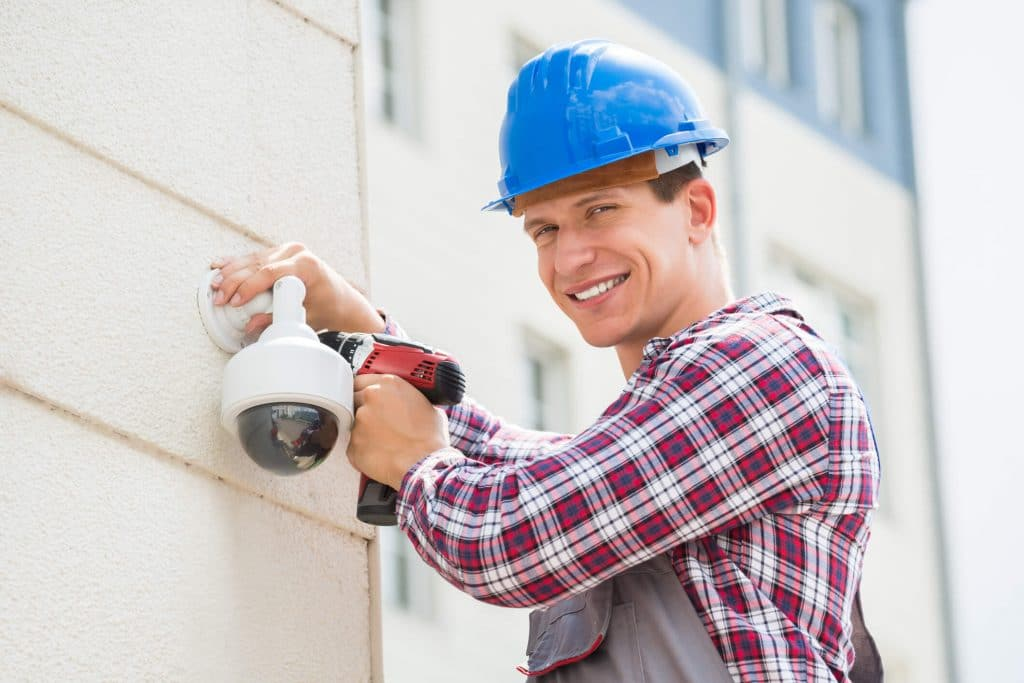 Denver property manager installing an outdoor video camera